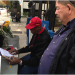 John with street vendor signing our petition.
